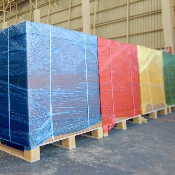 large warehouse pallets wrapped in solid colored shrink wrap, blue, red, yellow, and green