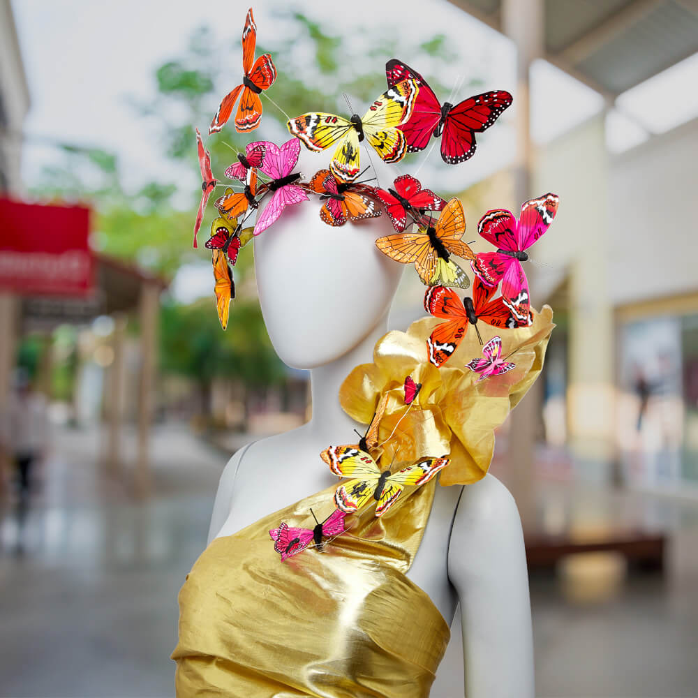 mannequin wearing a gold bodice and facing to the left wearing a crown of pink, red, and yellow butterflies from Paper Mart