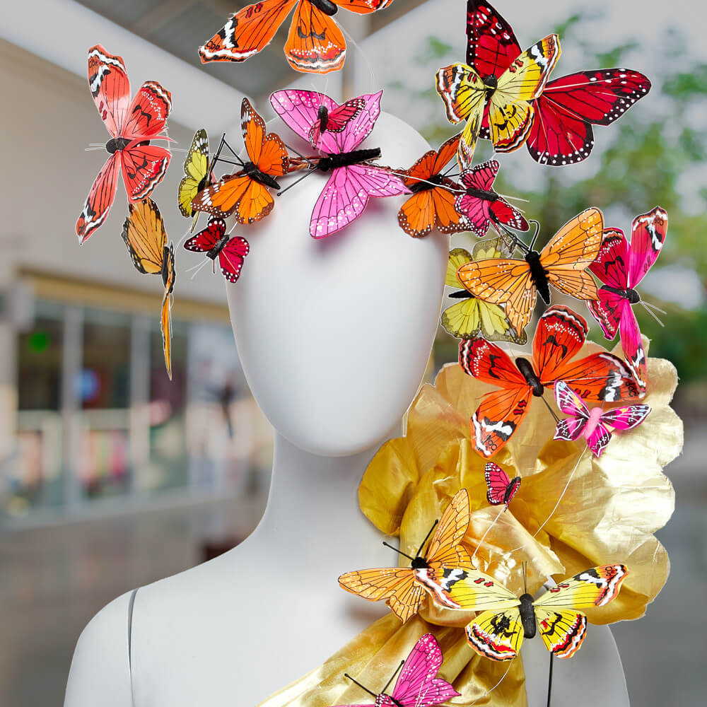 window display idea, mannequin facing forward wearing a crown of pink, red, and yellow butterflies