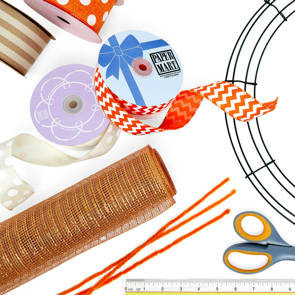 flat lay of materials and supplies to make an Easter wreath, paper mart ribbons, deco mesh, and round wreath frame