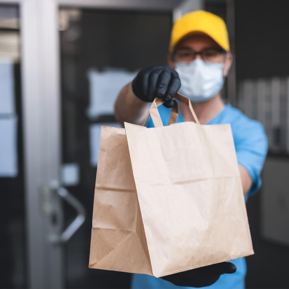 person with a protective mask and gloves on holding a paper bag