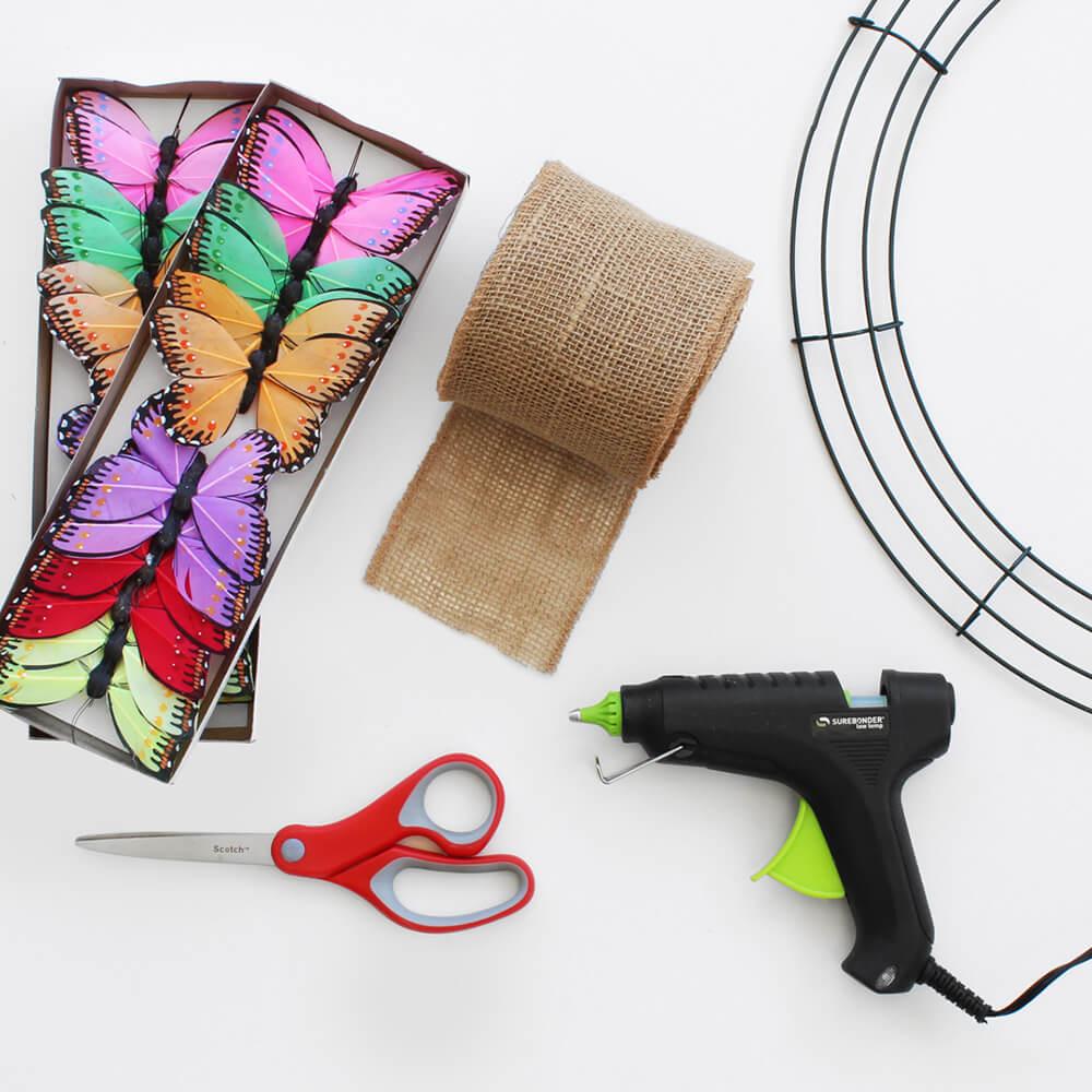 flat lay of paper mart butterflies, natural jute ribbon, and hot glue gun