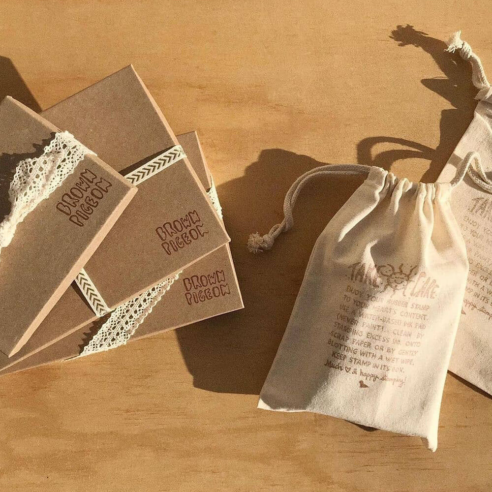 flat lay photo of Paper Mart kraft boxes and muslin bags stamped with Brown Pigeon stamps