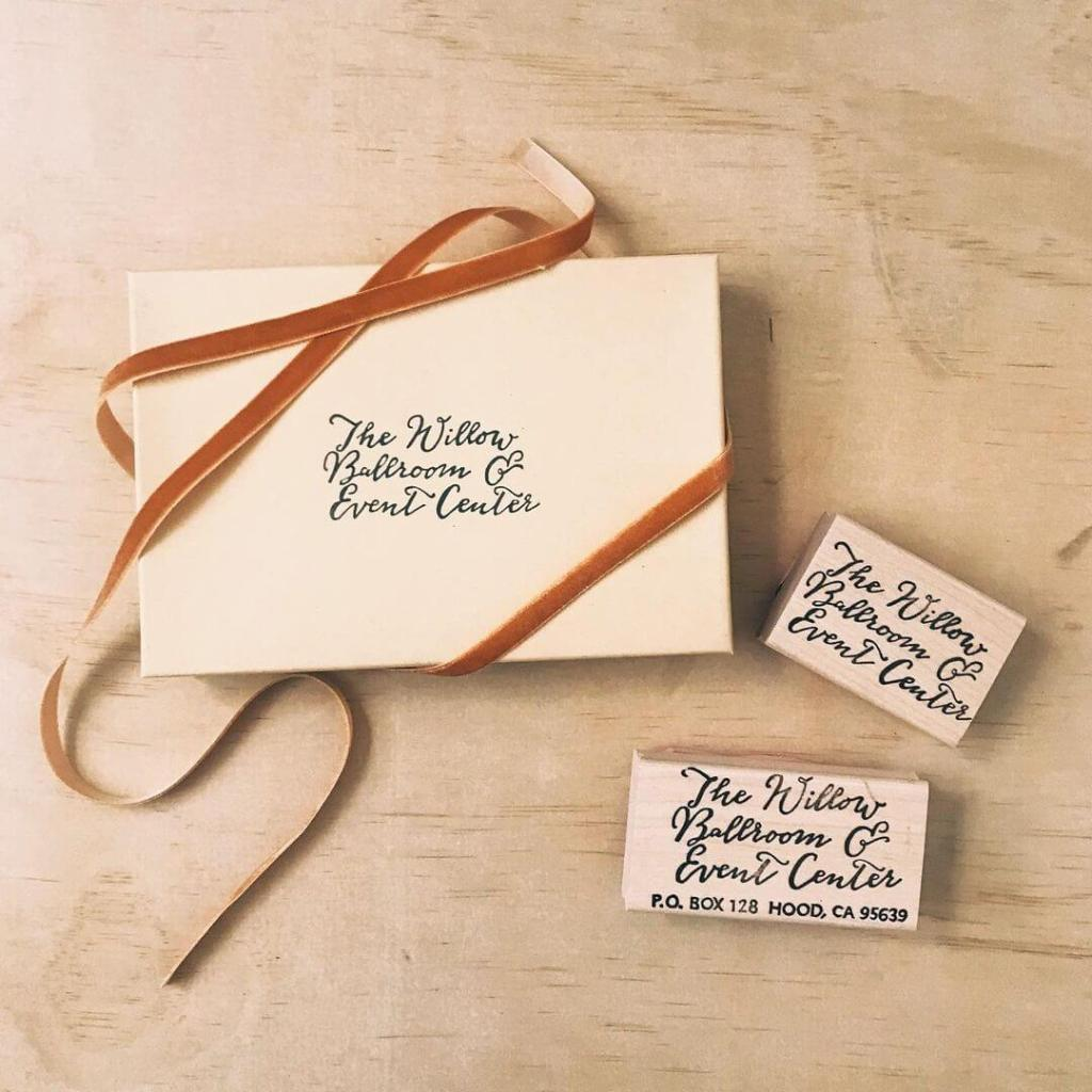 Paper Mart kraft box covered with a narrow velvet ribbon alongside Brown Pigeon stamps