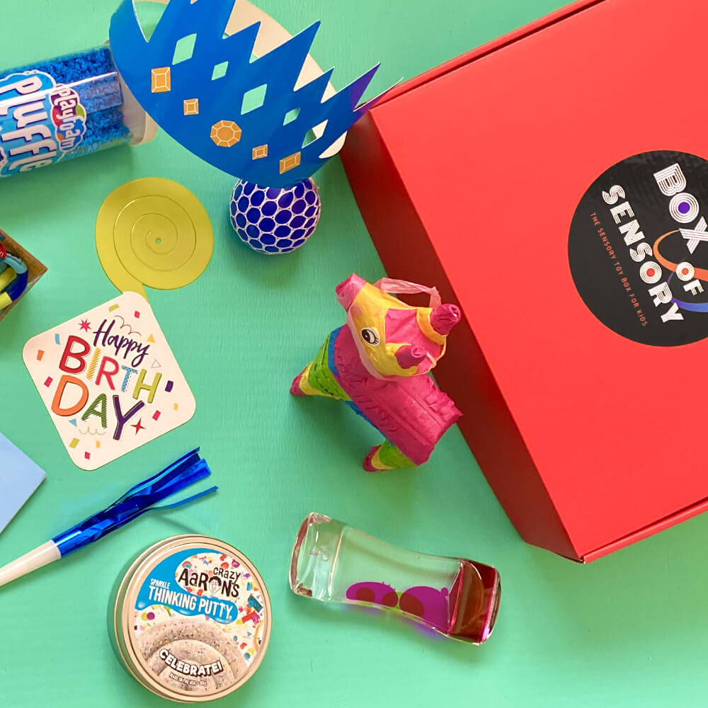 flat lay of sensory toys next to a Paper Mart matte colored corrugated shipping box