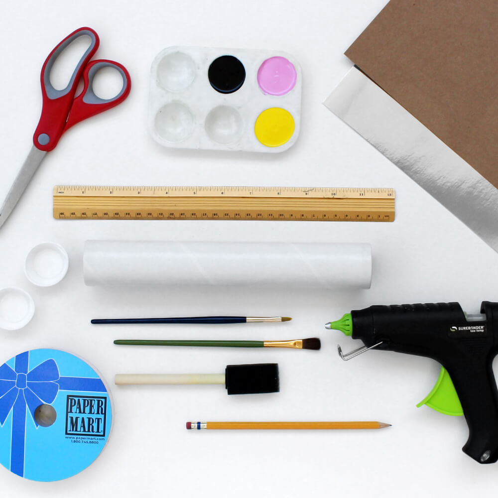 flat lay of paper mart craft supplies - mailing tube, poster board, hot glue, and ribbon