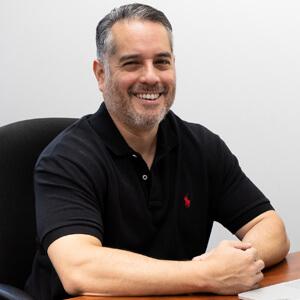 paper mart team member smiling at their desk