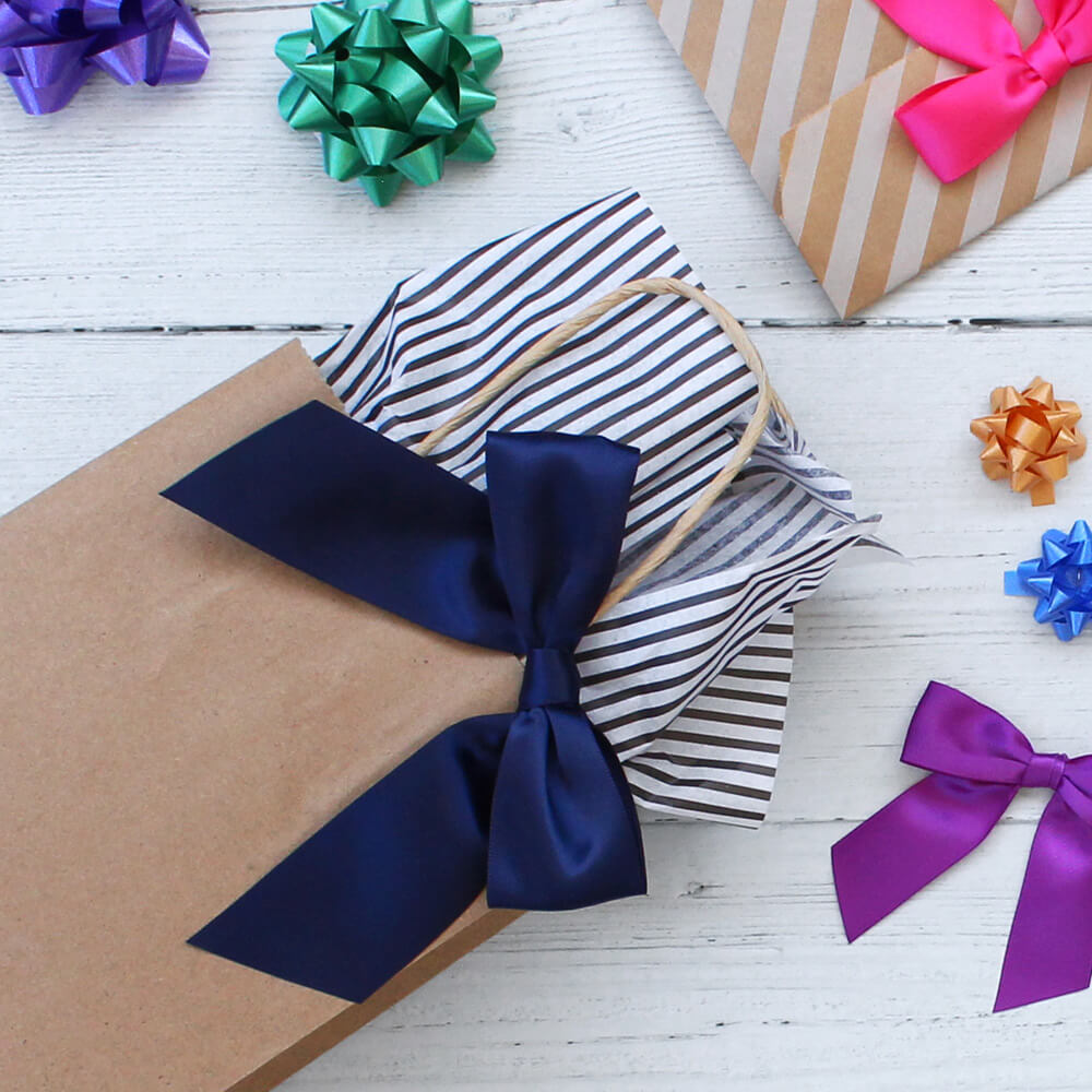 paper handled gift bag with striped tissue paper flat lay surrounded by confetti bows