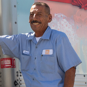 Paper Mart Delivery Driver smiling in front of their truck