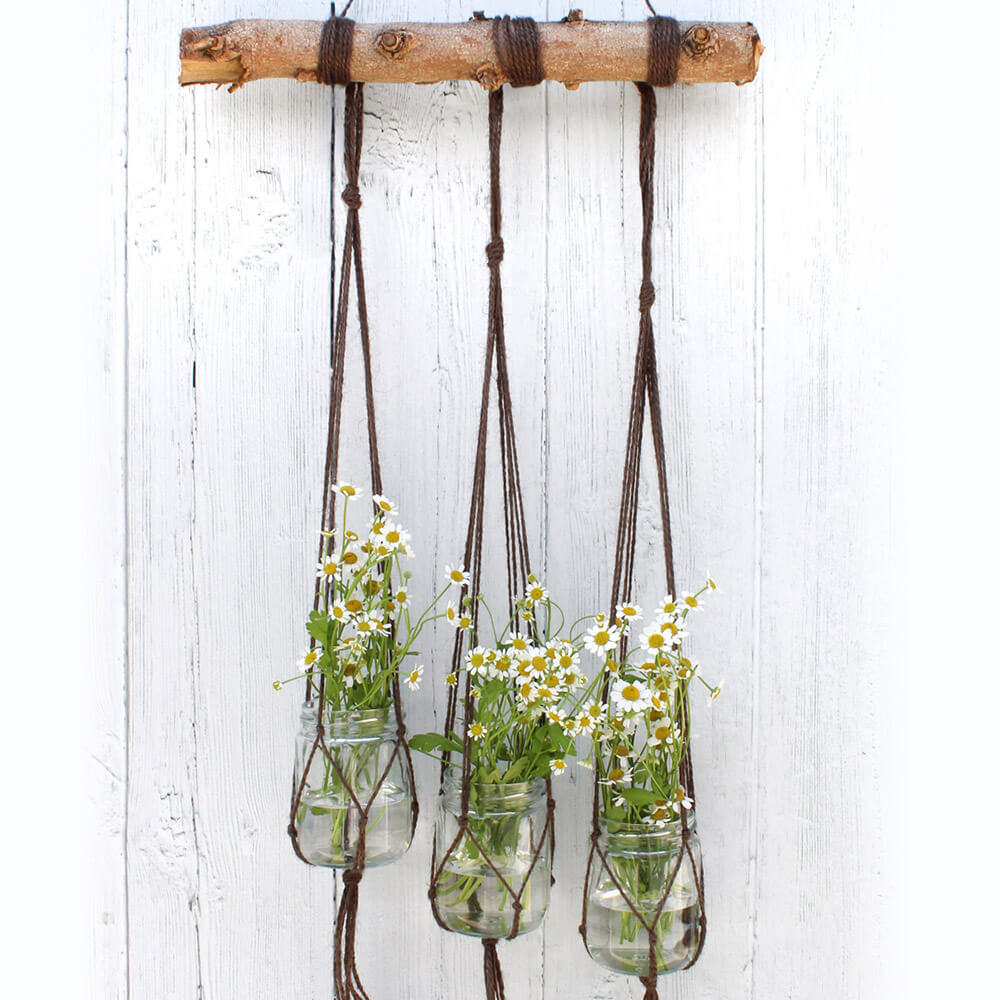 styled photograph of three jars filled with flowers, hanging from three macrame plant hangers