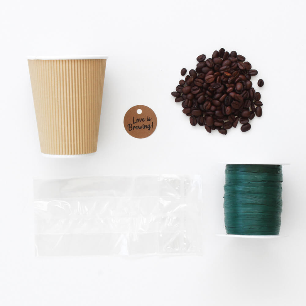 flat lay of coffee cup gift with cello bag, raffia ribbon, coffee grounds, and label