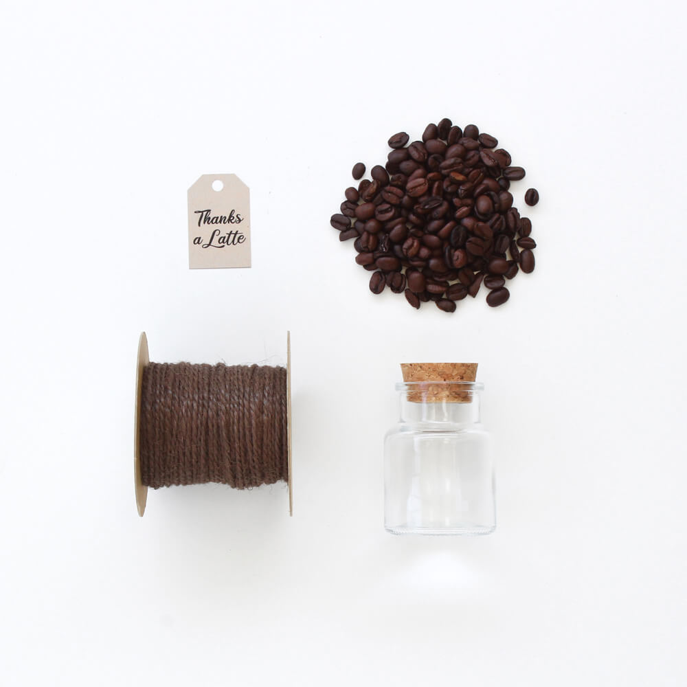 flat lay of coffee favor with jar, jute cord, coffee grounds, and label