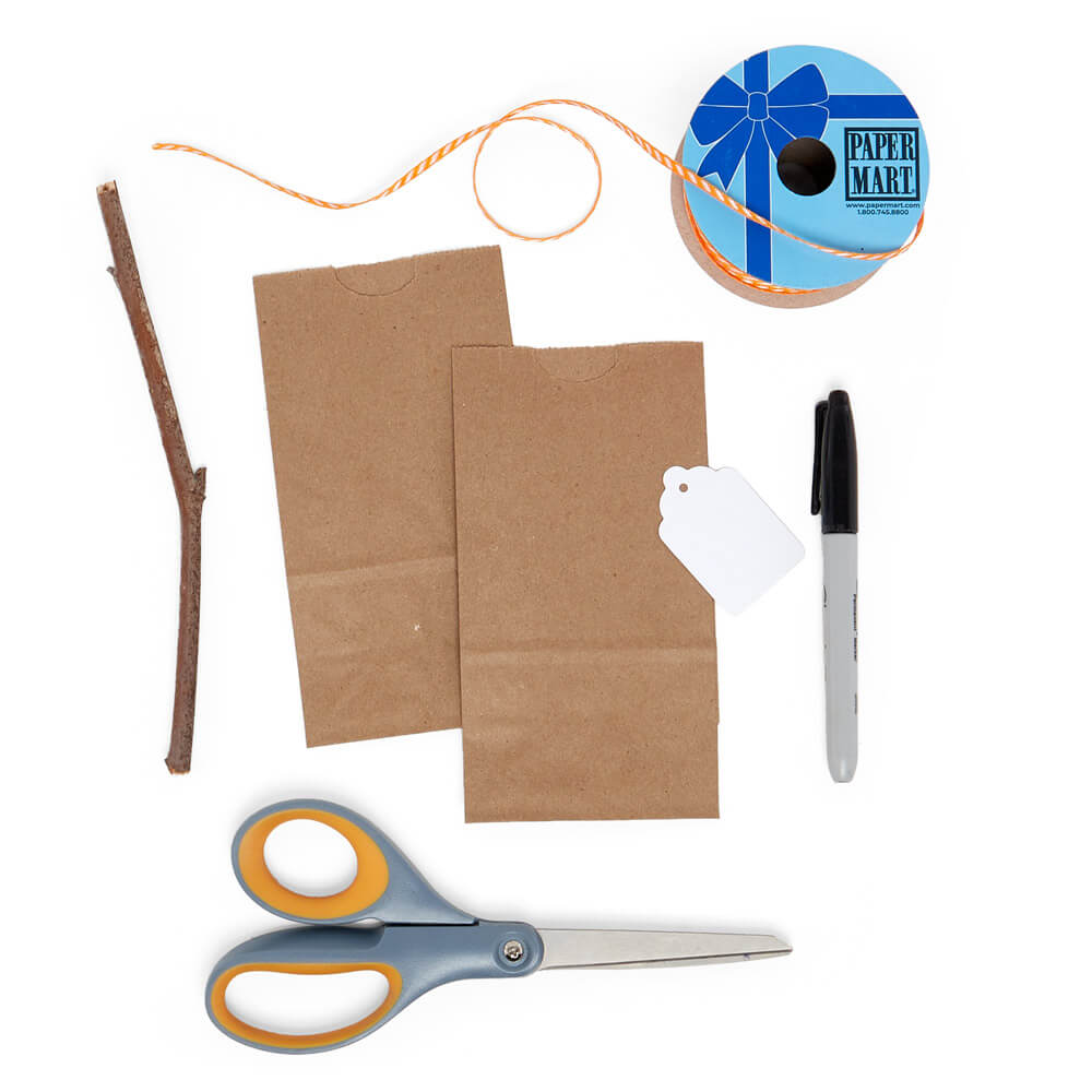 craft supply flat lay of two kraft grocery bags, a white merchandise tag, and a paper mart narrow ribbon