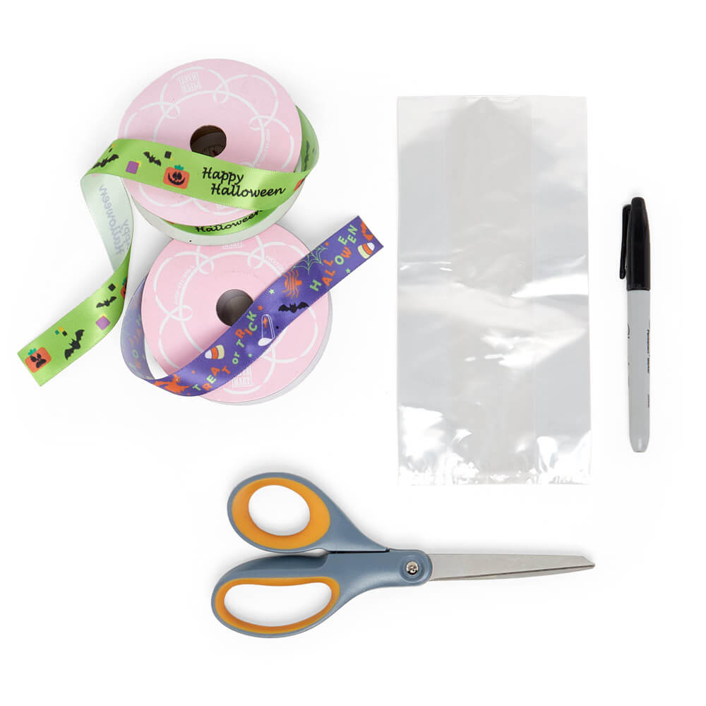 flat lay of paper mart craft supplies, satin ribbons, scissors, and clear gusseted cello bag