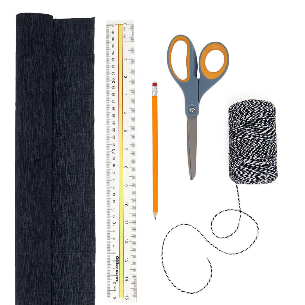 craft supply flat lay of a roll of paper mart crepe paper, roll of black and white bakers twine, a ruler, pencil, and scissors