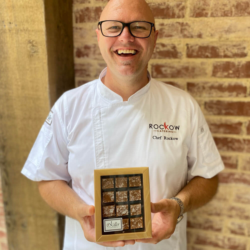 Jeff Rockow of Rockow Catering holding a Paper Mart candy box filled with Killer Caramels